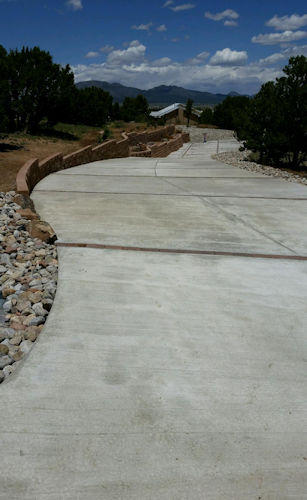 Long concrete driveway, landscaping, by Rising Sun Landscaping & Maintenance