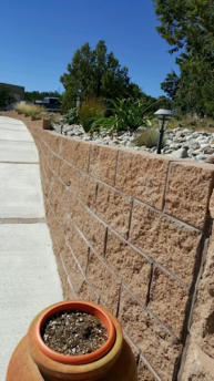 Block retaining wall and concrete walkway by Rising Sun Landscaping & Maintenance