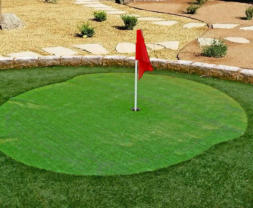 Back yard putting green with synthetic grass by Rising Sun Landscaping & Maintenance.